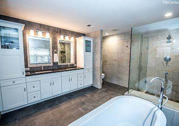Bathroom remodeling with black countertop and shower glass doors
